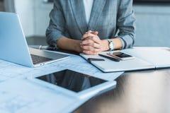 image cultivée de femme d'affaires se reposant à la table dans le bureau avec les dispositifs numériques image stock