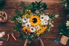 image cultivée de fleuriste mettant le bouquet des fleurs photos stock