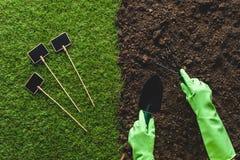 image cultivée de jardinier dans les gants protecteurs fonctionnant avec des outils de jardinage et des tableaux noirs vides sur  Photo stock