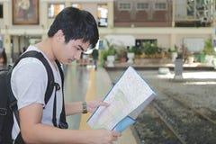 Image cultivée de jeune touriste asiatique avec un sac regardant la carte dans la station de train avec le fond de l'espace de co Photos stock