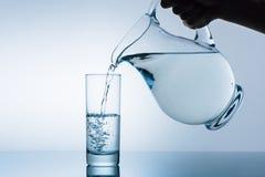 Image cultivée de l'eau de versement de femme de la cruche photo stock