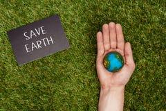 image cultivée de l'homme jugeant le modèle de la terre disponible avec la terre d'économies de signe sur l'herbe verte, la terre illustration de vecteur