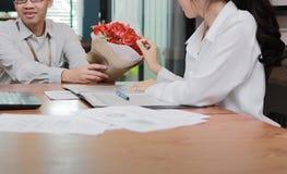 Image cultivée de la jeune femme asiatique attirante acceptant un bouquet des roses rouges de l'ami dans le bureau le jour du ` s Images libres de droits