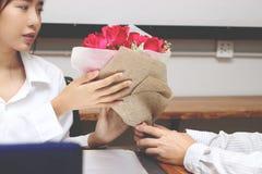 Image cultivée de la jeune femme asiatique attirante acceptant un bouquet des roses rouges de l'ami dans le bureau le jour du ` s Images stock