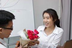 Image cultivée de la jeune femme asiatique attirante acceptant un bouquet des roses rouges de l'ami dans le bureau le jour du ` s Photos stock