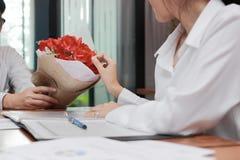 Image cultivée de la jeune femme asiatique attirante acceptant un bouquet des roses rouges de l'ami dans le bureau le jour du ` s Image libre de droits