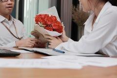 Image cultivée de la jeune femme asiatique attirante acceptant un bouquet des roses rouges de l'ami dans le bureau le jour du ` s Photos libres de droits