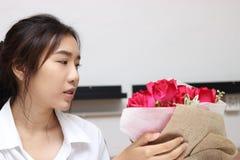 Image cultivée de la jeune femme asiatique attirante acceptant un bouquet des roses rouges de l'ami dans le bureau le jour du ` s Image stock