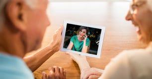 Image cultivée de la vieille vidéo de couples appelant par le comprimé numérique à leur fille grande à la maison photographie stock