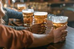 image cultivée de société tenant des verres avec de la bière Images libres de droits