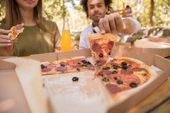 Image cultivée des étudiants multi-ethniques d'amis buvant du jus mangeant de la pizza Photos stock