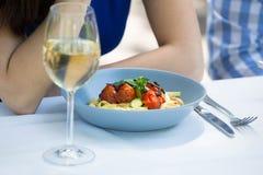 Image cultivée des ajouter à la nourriture et au verre à vin sur la table Photographie stock
