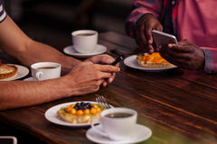 Image cultivée des amis mangeant des pâtisseries et buvant du café Images stock