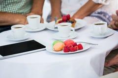 Image cultivée des amis s'asseyant par la table dans le restaurant Image stock