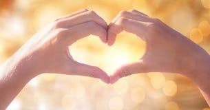 Image cultivée des couples faisant la forme de coeur avec des mains contre le bokeh Images libres de droits