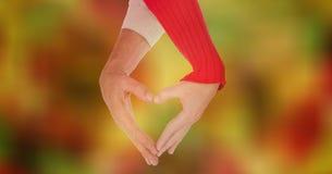 Image cultivée des couples faisant la forme de coeur avec des mains contre le bokeh Image libre de droits