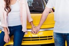 Image cultivée des couples tenant des mains devant nouveau photos stock