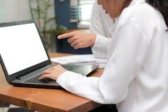 Image cultivée des gens d'affaires assidus travaillant ensemble sur un ordinateur portable au bureau Concept brainstroming de tra Photographie stock libre de droits