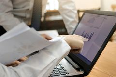 Image cultivée des gens d'affaires assidus travaillant ensemble sur un ordinateur portable au bureau Concept brainstroming de tra Image libre de droits