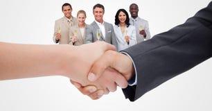 Image cultivée des gens d'affaires faisant la poignée de main avec des employés tenant le champagne à l'arrière-plan Photo stock