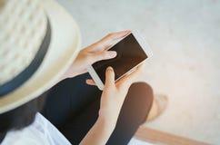 Image cultivée des mains de la femme tenant le téléphone intelligent avec c vide Photos stock