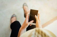 Image cultivée des mains de la femme tenant le téléphone intelligent avec c vide Photos libres de droits