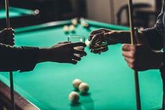 image cultivée des mains masculines avec des queues et des verres avec de l'alcool devant la table de billard Photos stock