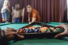 image cultivée des mains masculines formant l'ensemble de boules de billard Image libre de droits