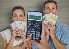 Image cultivée des mains utilisant la calculatrice contre des couples tenant des devises Images libres de droits