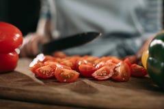 image cultivée des tomates-cerises de coupe de cuisinier photographie stock