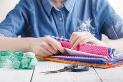 Image cultivée du beau jeune concepteur travaillant avec les croquis et la bande de mesure dans le salon de couture Photo libre de droits