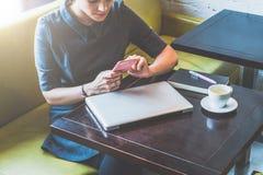 Image cultivée Jeune femme d'affaires s'asseyant en café à la table et au smartphone d'utilisation Image libre de droits