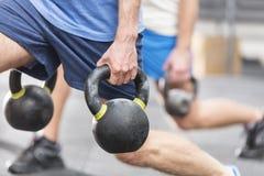Image cultivée des hommes soulevant des kettlebells au gymnase de crossfit Photos stock