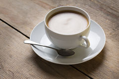 Image of a cup of coffee on a suacer with an old vintage spoon and a vanilla cookie, placed on a wooden table top Stock Images