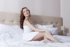 Image of curly brunette posing in hotel bed Stock Photos