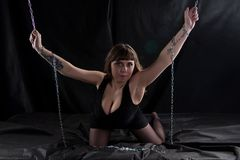 Image of curvy woman holding chains. On black background royalty free stock photo
