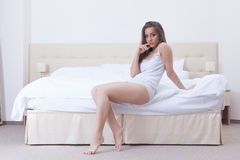 Image of curvy young girl sitting on hotel bed Stock Photos