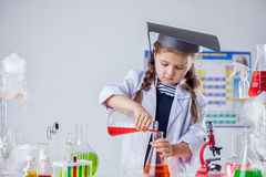 Image of cute chemist pours reagent into flask Royalty Free Stock Photo