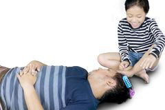 Cute child playing with her father asleep. Image  of cute child with her asleep father while playing hair rollers, isolated on white background Royalty Free Stock Photography