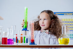 Image of cute girl posing with colorful flasks. Close-up stock images