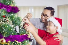 Little boy decorating Christmas tree with his father. Image of cute little boy decorating a Christmas tree with his father and having fun together. Shot at home royalty free stock photos