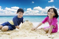 Cute little girl with her brother playing sand. Image of a cute little girl with her brother smiling at the camera while playing sand together on the tropical Stock Image