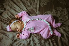 Image of cute little girl in pink suit indoor. Royalty Free Stock Photos