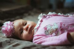 Image of cute little girl in pink suit indoor. Royalty Free Stock Photography