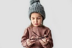 Image of cute little girl playing in the winter warm hat, wearing sweater with round stylish spectacles on a white studio. Background royalty free stock photo