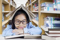 Cute schoolgirl sitting in the library. Image of cute schoolgirl looking at the camera with a book over her head while sitting in the library Royalty Free Stock Photos