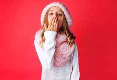 The image of a cute teenage girl in a white sweater standing isolated on a pink background sends a kiss , wearing a warm pink hat royalty free stock photos