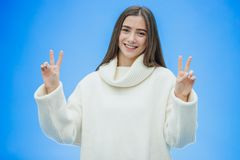 Image of cute young lady standing isolated over blue background. Looking camera showing peace gesture. stock image