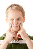 Image of a cute young male with fake smile. Isolated over white background Royalty Free Stock Photo