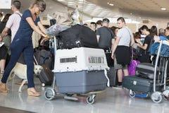 Image d'éditorial de Documantary Bagage d'aéroport avec des valises, femme non identifiée d'homme marchant dans l'aéroport, stati Images libres de droits